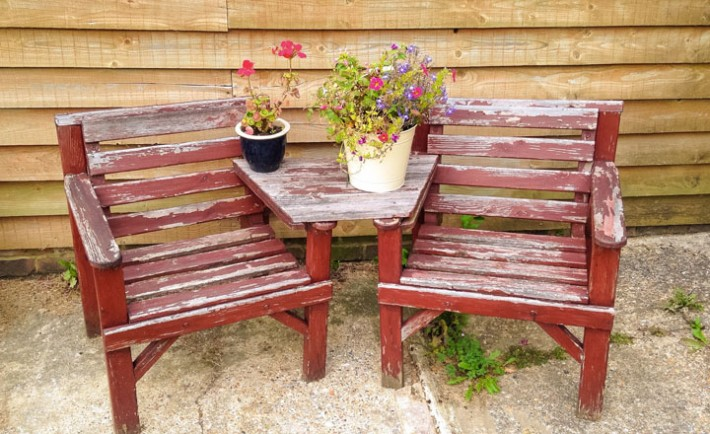 Two old rustic wooden chairs on a patio with a pretty flower arrangement make the perfect place to relax in the summer sun.
